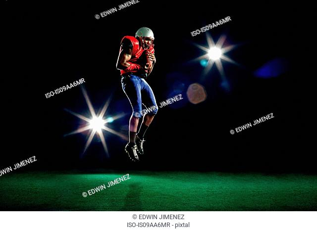 American football player mid air with ball