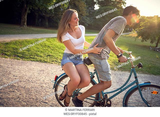 Young couple riding bicycle in park, woman sitting on rack