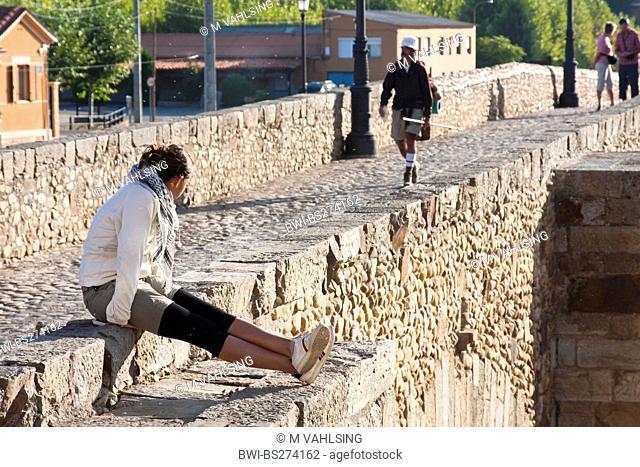 morning arrival of a pilgrim on the mediaeval bridge 'Puente de rbigo', Spain, Kastilien und Len, Hospital de rbigo