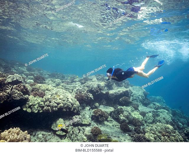 Caucasian woman snorkeling near coral reef in tropical ocean