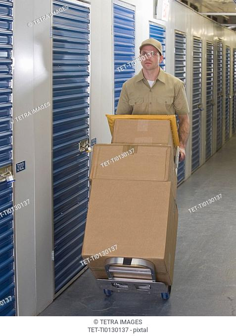 Delivery man pushing stack of packages