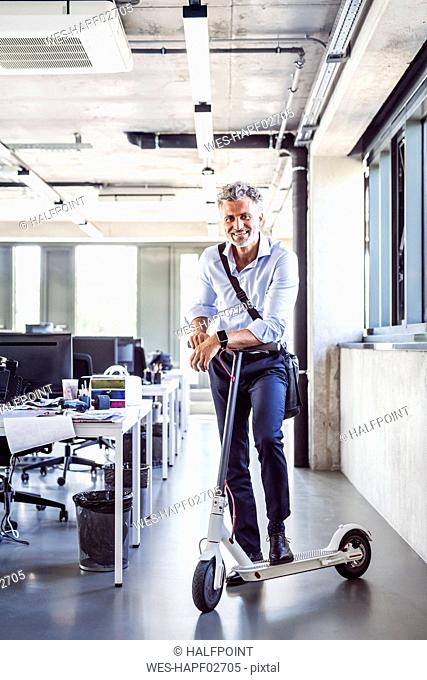 Portrait of happy mature businessman with scooter in office