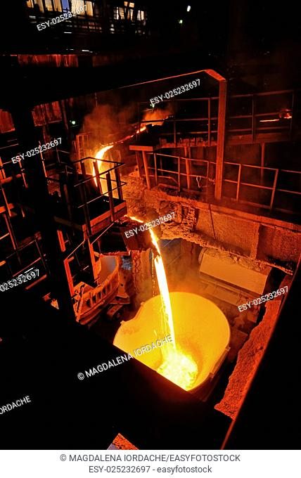 pouring molten steel in steel ladle