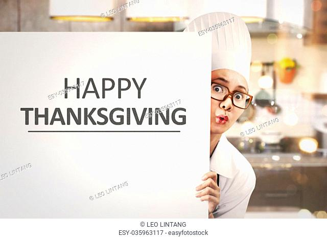 Young asian woman chef holding white banner with Happy Thanksgiving message in the kitchen