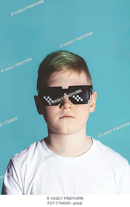 Boy wearing sunglasses against blue background
