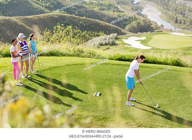middle-aged female golfer teeing off while friends watch