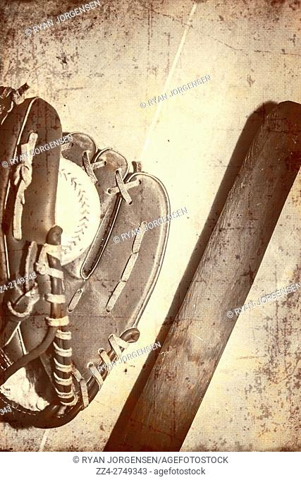 Vintage nostalgic sepia toned image of a old baseball bat, mitt and ball on a wooden background with copy space