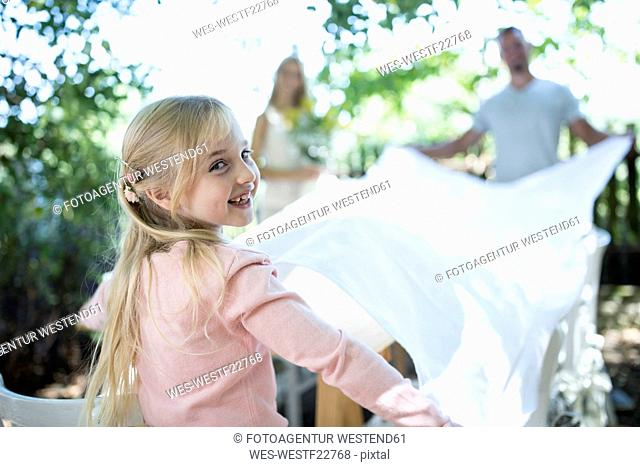 Smiling girl with her parents spreading out tablecloth in garden