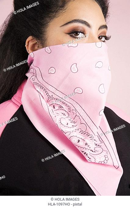 Young woman with pink bandana over face
