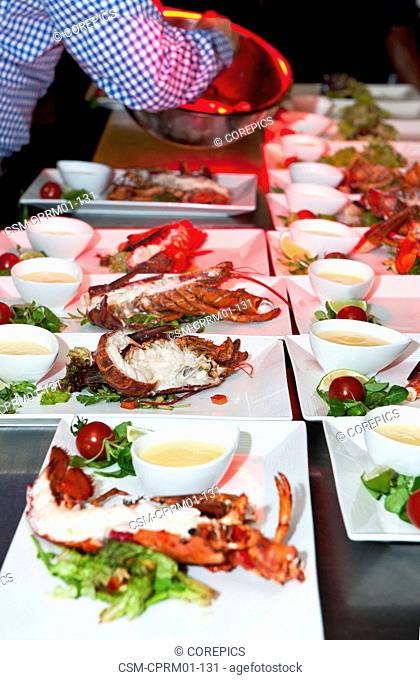 Plates with lobster being prepared in a restaurant kitchen by a chef, garnishing salad from a bowl