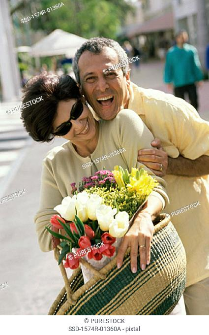 Portrait of a couple smiling holding a bouquet of flowers