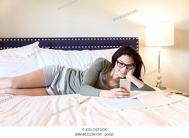 Caucasian woman laying on bed texting on cell phone