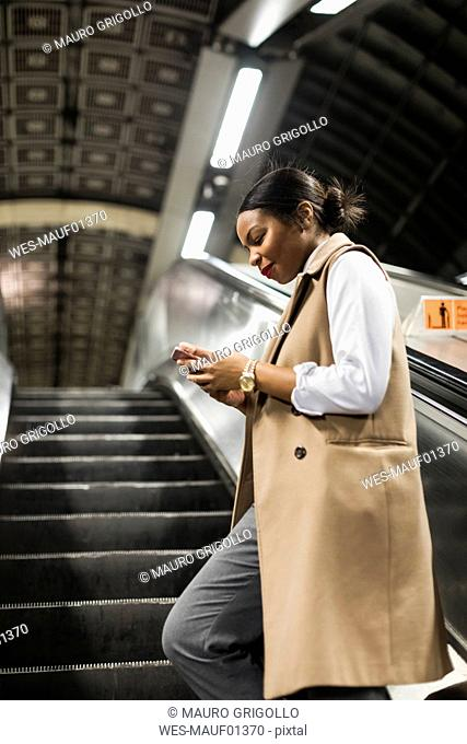 UK, London, smiling businesswoman standing on escalator of underground station looking at cell phone