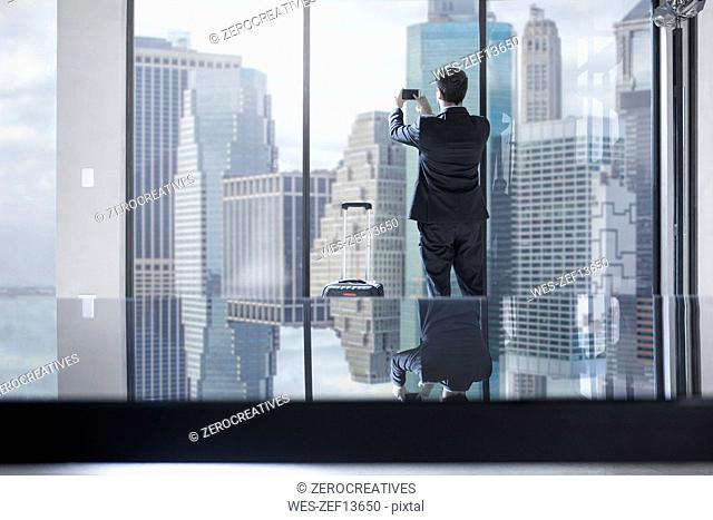 Businessman with rolling suitcase taking photos of city view in office