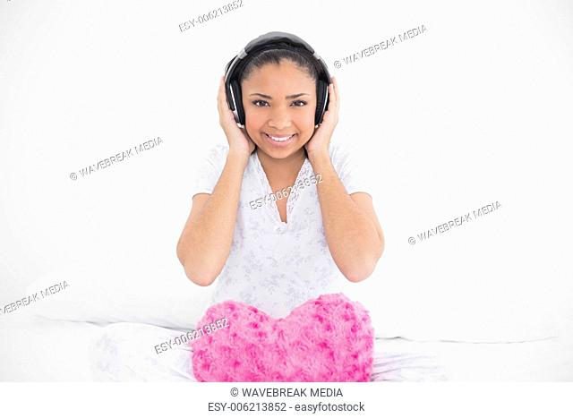 Cheerful young dark haired model listening to music with headphones