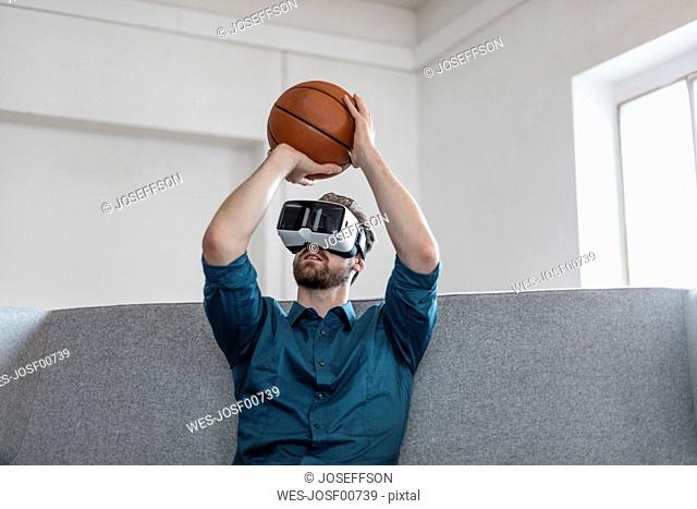 Young man with basketball sitting on couch using Virtual Reality goggles