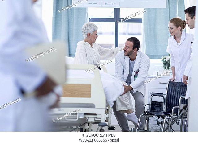 Doctor and staff helping patient with wheelchair in hospital