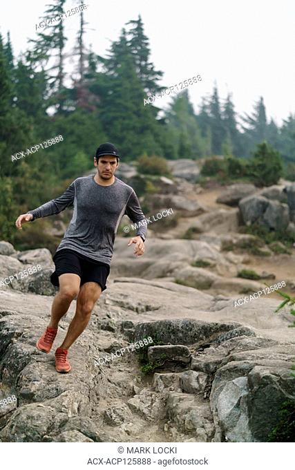 A young male trail runner running through Cypress Provincial Park, British Columbia, Canada