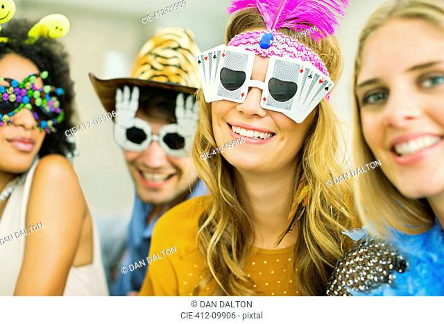 Friends wearing decorative glasses at party