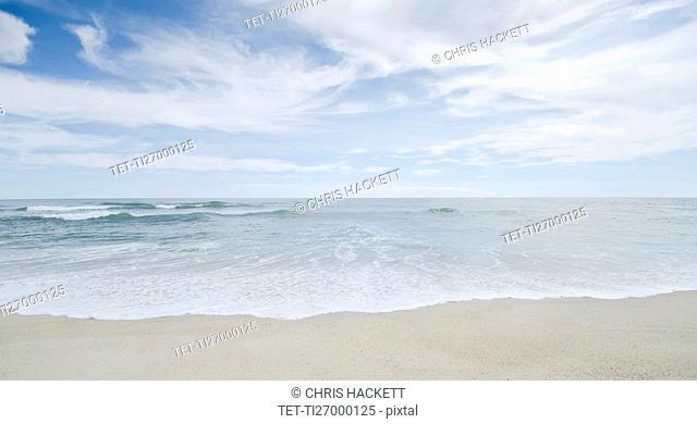 Seascape with surf on sandy beach