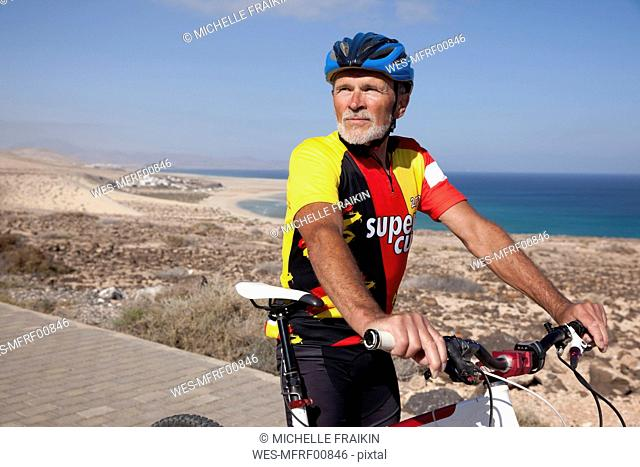 Spain, Canary Islands, Fuerteventura, senior man with mountainbike having a rest