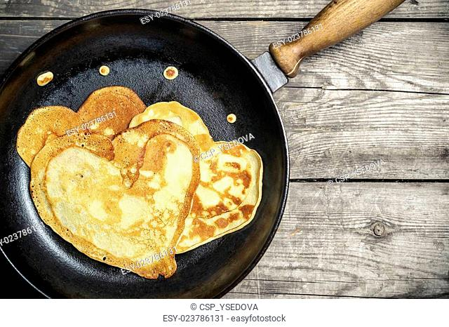 Fried pancakes - heart on a cast iron skillet . Top view