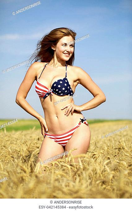 Back view, beautiful blonde woman in sexy American flag bikini in a wheat field