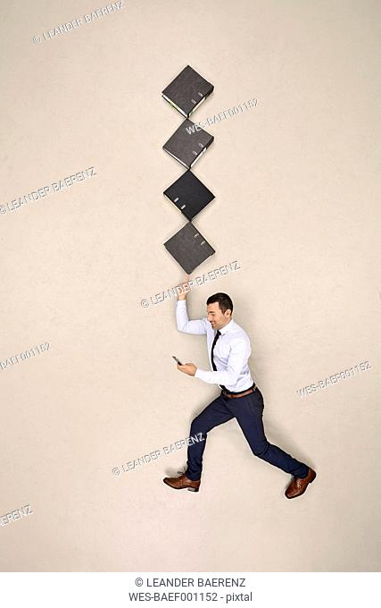Businessman balancing folders on his finger while texting