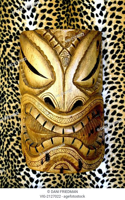 UNITED STATES OF AMERICA, MAUI, 07.07.2007, A Hawaiian Tiki mask against a leopard print background. - MAUI, HAWAII, UNITED STATES OF AMERICA, 07/07/2007