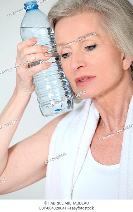 Portrait of senior woman with bottle of water after exercising