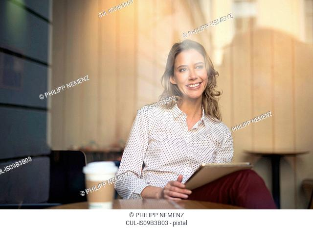 Mid adult woman in cafe window seat using digital tablet