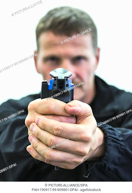 16 September 2019, Rhineland-Palatinate, Mainz: Martin Bronder, a law enforcement officer, holds a pepper spray spray in his hands during a press conference at...