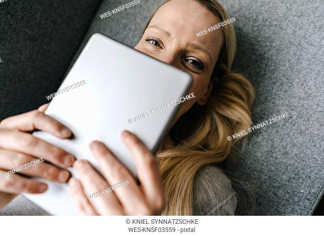 Portrait of smiling woman lying down holding tablet