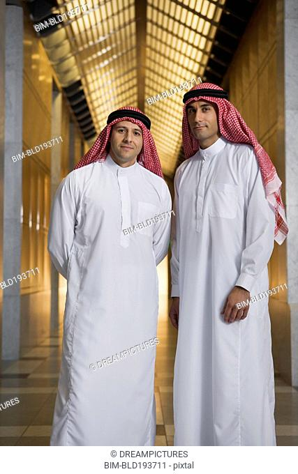 Middle Eastern men in traditional clothing in corridor