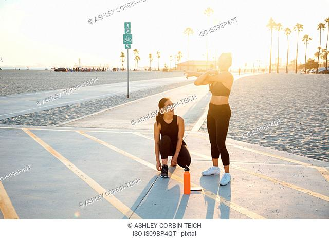 Friends doing exercises by beach, Long Beach, California, US