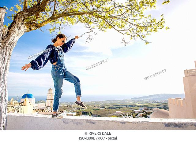 Girl balancing on top of wall, Oía, Santorini, Kikladhes, Greece