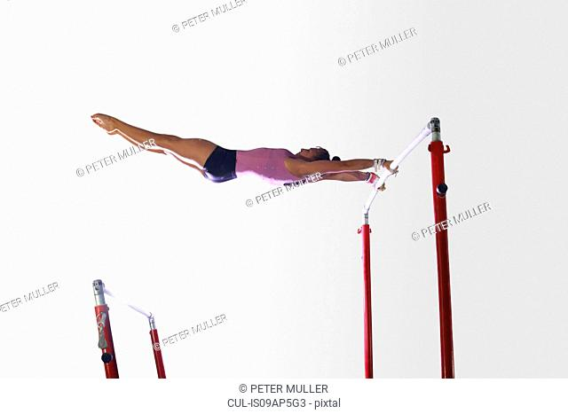Young gymnast performing on uneven bars