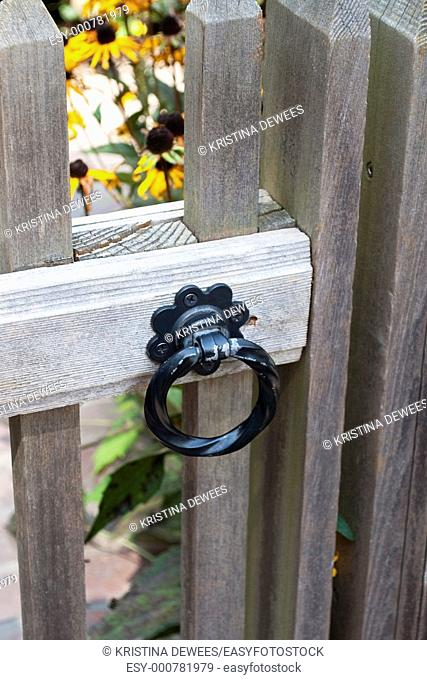 The round latch of a wooden gate leading into a garden of black eyed susans