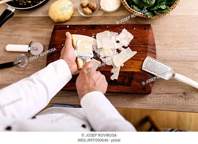 Chef preparing stuffing for ravioli, slicing parmesan cheese