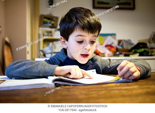 child sitting at the table in the kitchen at home with book