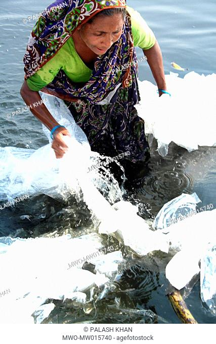 A woman cleans dirty polythene in the Buriganga The water of the river has become polluted beyond threat level by the city's wastes and such activities Dhaka