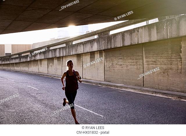 Female runner running into urban tunnel