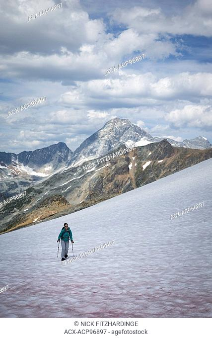 A young female snowshoeing uphill approaching Asulkan Pass, Glacier National Park, British Columbia, Canada