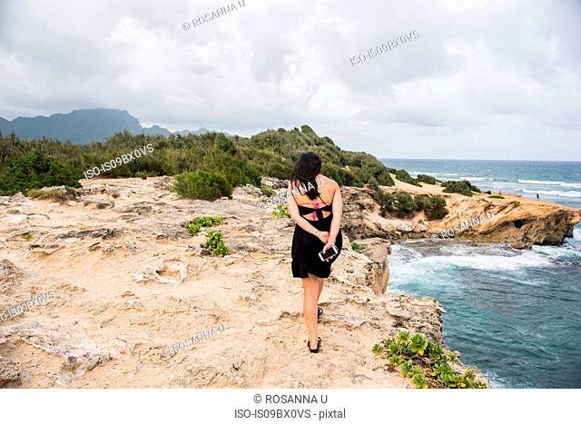 Woman walking with cellphone in hand, Shipwreck Beach, Kauai, Hawaii