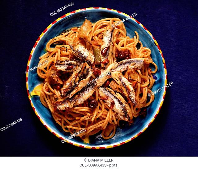 Sardines with spaghetti in bowl, overhead view
