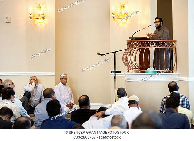 Adult Muslim men gather for afternoon prayers at an Anaheim, CA, mosque. Note Iman conducting the service. The sermon is also called the Khutbah