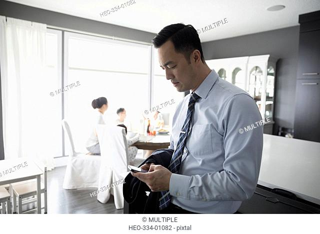 Businessman father checking cell phone in dining room