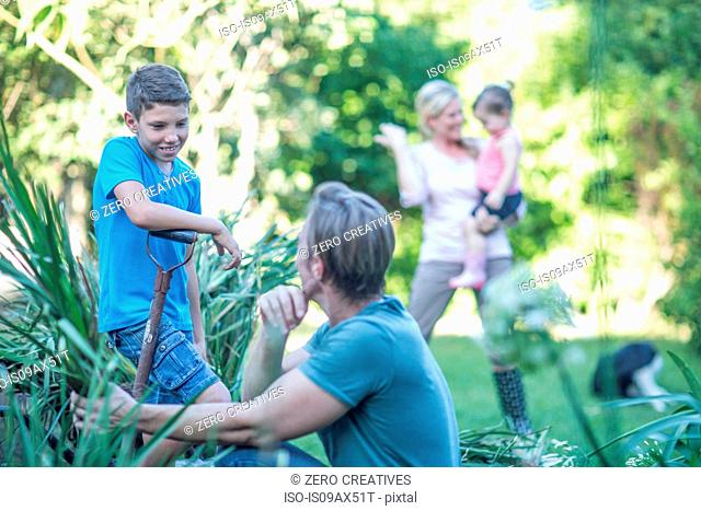 Family in garden together, father and son doing gardening