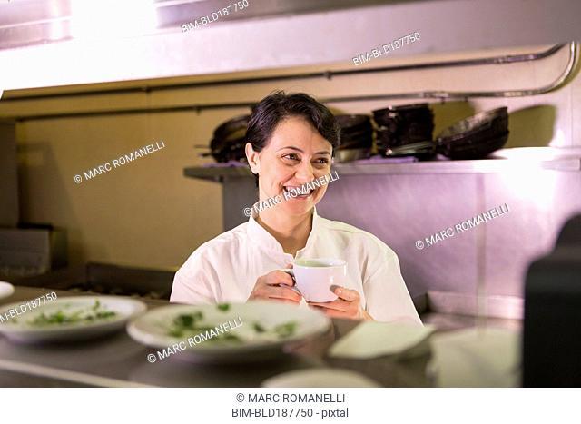 Caucasian chef smiling in restaurant kitchen