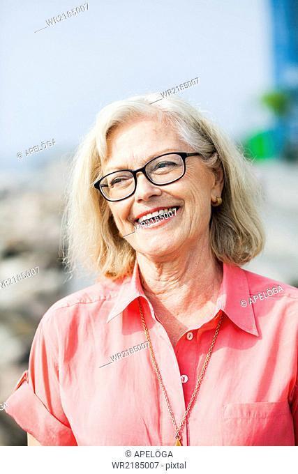 Smiling senior woman wearing glasses outdoors